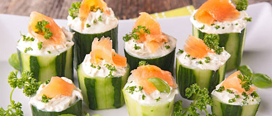 Cucumber appetizer with green leaves and salmon pieces for heavy appetizers